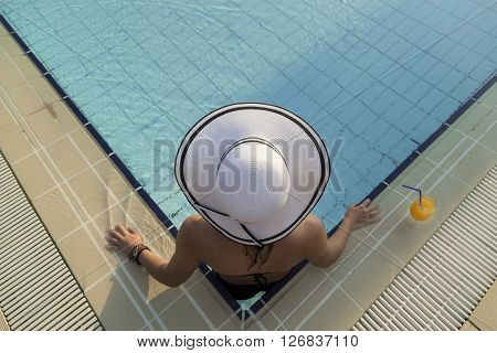 Girl with a hat on the edge of a swimming pool looking away from the camera enjoying the sun water and drinking juice