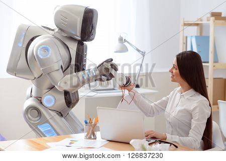 Nice device. Cheerful delighted positive woman sitting at the table and expressing gladness while robot giving headphones to her