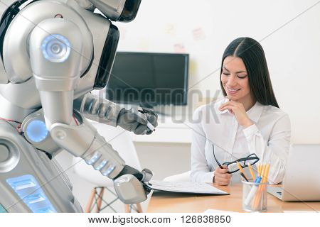 Documents for you. Cheerful smiling delighted woman sitting at the table while robot holding folder and giving it to her