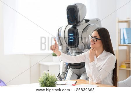 Mind it. Cheerful delighted charming girl sitting at the table and pointing up while robot standing nearby