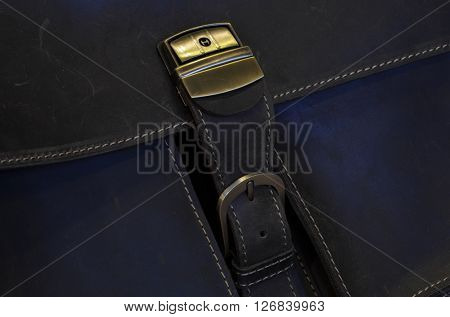 Metal clasp on old leather case with stitching