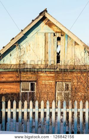 Old derelict wooden house with broken wood slats and windows.