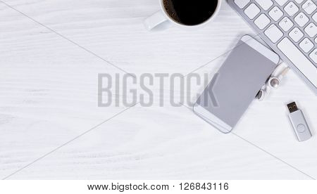 Overhead view of white desktop with partial computer keyboard cell phone coffee thumb drive and ear phone.