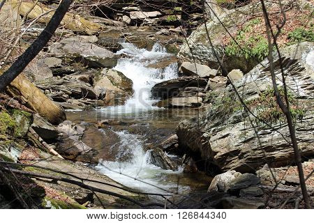 A Creek and boulders. Water running through and around large boulders.