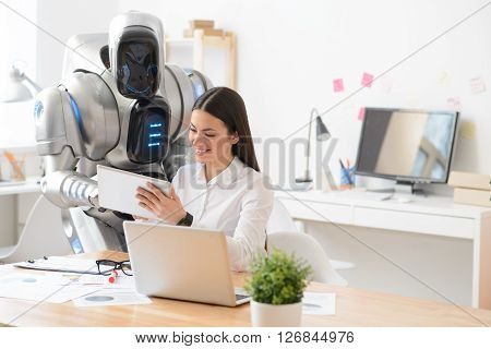 Work together. Pleasant charming delighted girl sitting at the table while using tablet with the robot