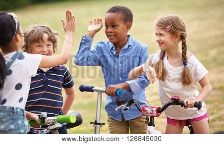 Happy kids high five each other at the park