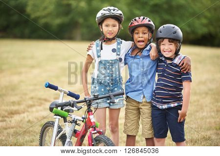 Interracial group of children with bike and scooter in summer