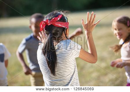 Kids having fun playing blind man's buff at the park
