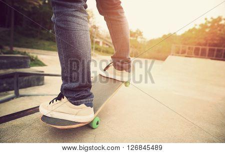 young skateboarder legs riding on skateboard at skatepark