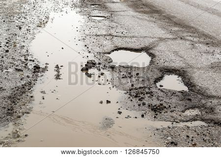 Large Pot Holes On A Rain Soaked Road
