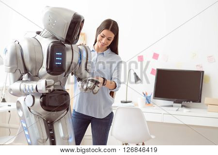 I support you.  Delighted smiling attractive woman expressing joy and holding hand of the robot while standing in the office