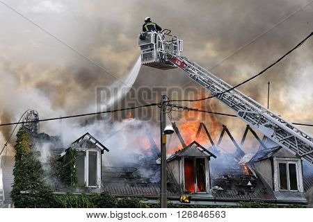 Fire fighter fighting a burning house with water