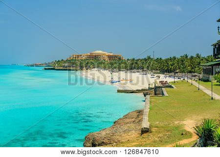 Varadero island beach, Cuba, Apr. 30, 2014: Beautiful, amazing, charming wide open view of tranquil ocean, green cliffs with gorgeous white sand palm beach and walking people in background.