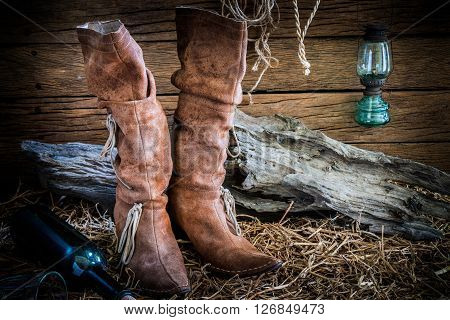 Still life photography with traditional leather boots in vintage ranch barn background