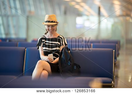 Woman Using Cell Phone In Airport Waiting Lounge