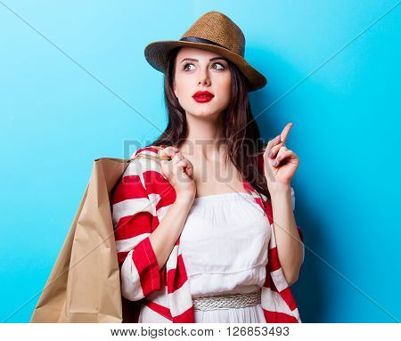 portrait of the beautiful young woman with shopping bags on the blue background