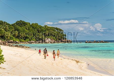 Anse Royale Mahe Island Seychelles - December 152015: People walking in the sand in Spectacular Anse Royale beach and in the background some people enjoying the Ance Royale Beach Mahe Island Seychelles.