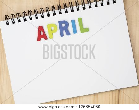 Word spelling month in the year April by wooden letters on notebook with wood background (Month name word series)