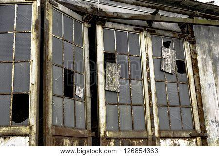 A close up broken glass doors on an abandoned building