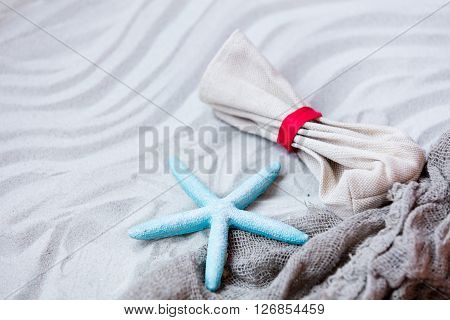 Starfish, Pouch And Fishnet On The Sand