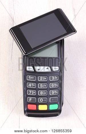 Credit card reader payment terminal and mobile phone with NFC technology on wooden background cashless paying for shopping or products