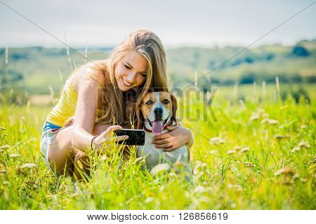 Young woman taking photo of herself and her pet with mobile phone camera