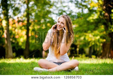 Tecnology in excess - teen girl calling with 2 mobile phones outdoor