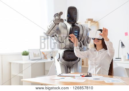 Involved in new reality.    Pleasant  beautiful content girl sitting at the table and using virtual reality device while robot standing nearby