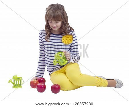 Pretty teengirl sitting with watering can and apples on white background