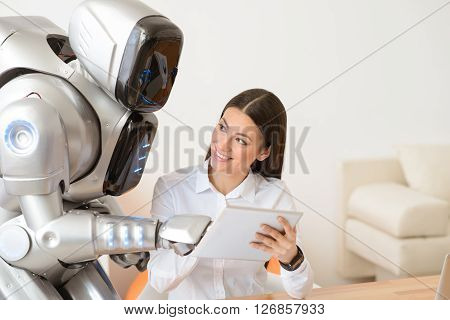 Digital touch. Cheerful delighted smiling woman sitting at the table and using together with robot tablet  while expressing joy
