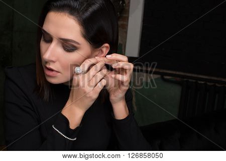The girl tries on earring, ring with a huge pearl bracelet, black background. She dresses in fashion in jewelry the interior