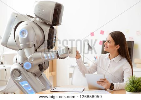 Pleasant thing for you. Robot bringing coffee to the woman who is sitting at the table and using tablet