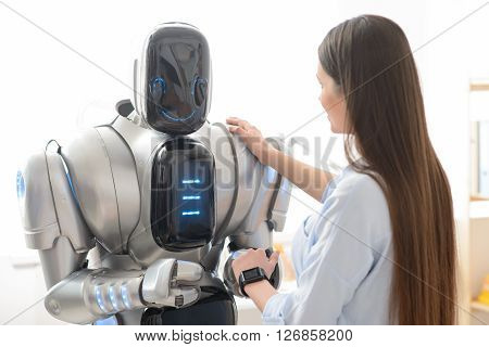 Nice to meet you. Pleasant delighted girl holding her hand on the shoulder on the robot while shaking hands