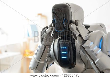 Switch on your mind.  Positive modern robot smiling and holding its hands on the head while expressing  gladness