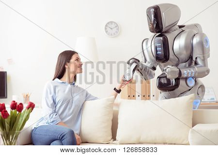 Your turn to listen.  Cheerful content beautiful girl sitting on the sofa and smiling while giving headphones to the robot