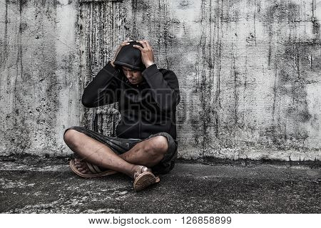 overdose asian male drug addict with problems man in hood with hands on his head