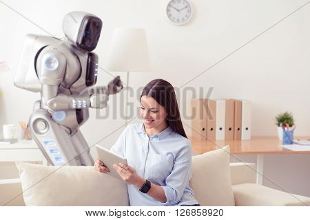 Day from the contemporary life.   Cheerful positive content smiling girl sitting on the couch and using tablet while her robot standing in the background