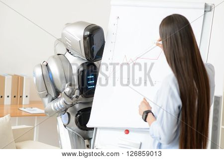 Follow my thought.  Pleasant  girl  drawing diagram while modern robot standing nearby and looking at it