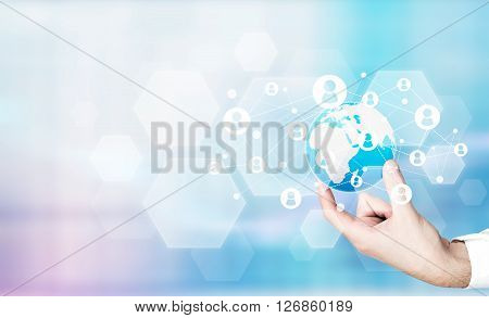 Male hand holding globe with networking system on light blue background
