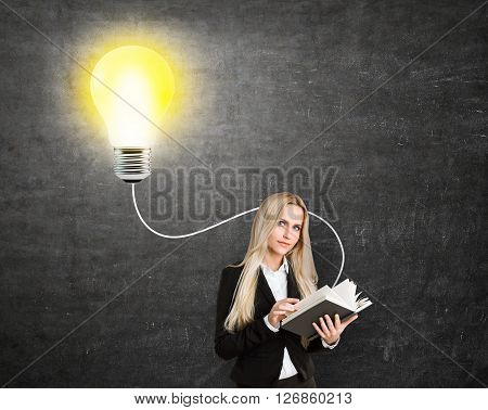 Idea concept with businesswoman and an illuminated lightbulb on blackboard background