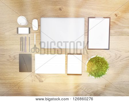 Topview of wooden desktop with closed laptop small plant and other office tools. Toned image. Mock up 3D Rendering