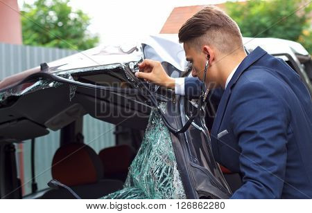 Well dressed insurance assessor inspecting damaged vehicle with a stethoscope