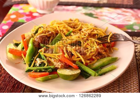thai spicy noodle with vegetables and chicken served on the street restaurant table