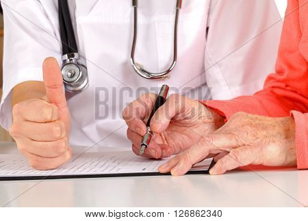 Senior hand signing on the medical examination form