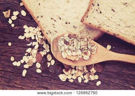 the cereal and black sesame bread with whole grain cereal flakes which mixed warming cinnamon red skin apple golden raisins and roasted hazelnuts on wooden plate