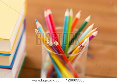 education, art, drawing, creativity and object concept - close up of crayons or color pencils and books on wooden table