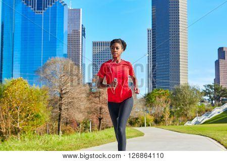 Runner girl running and listening music earphones in the city park