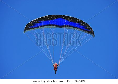 Paraglider unde his wing in a blue sky