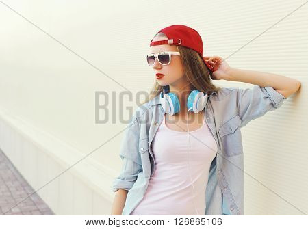 Pretty Woman In Red Cap And Sunglasses With Headphones Over White Background