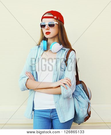 Pretty Woman In Sunglasses And Red Cap With Headphones Over White Background